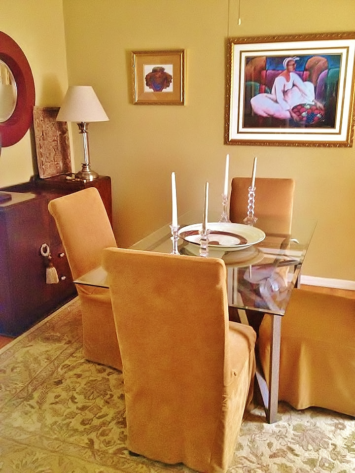 Maximize a small dining room using monochromatic colors. Add color with vibrant art, table settings and flowers.