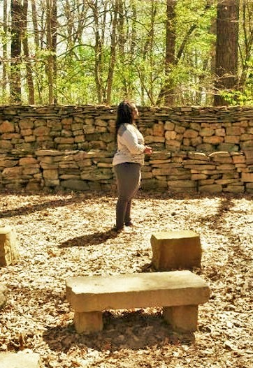 Nicole West pondering over the wisdom of ancestral stones at Wichahpi Stone Wall